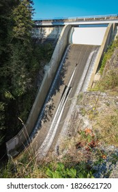 Cleveland Dam by Capilano Lake in North Vancouver, BC. Vertical view on the high dam with flowing water.