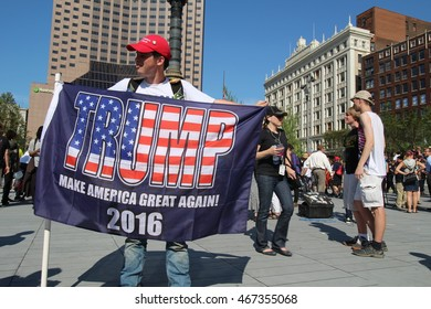 """Cleveland, OH July 19, 2016: Republican National Convention - A Trump supporter stands portraying his altered American Flag with the word """"Trump"""" Embedded."""