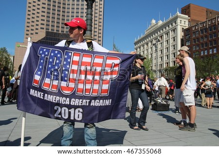"Cleveland, OH July 19, 2016: Republican National Convention - A Trump supporter stands portraying his altered American Flag with the word ""Trump"" Embedded."