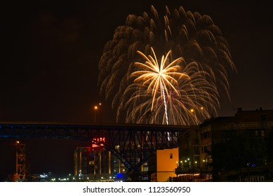 CLEVELAND, OH - JULY 4, 2016: A feathery burst of fireworks rises over downtown Cleveland's new Flats East Bank entertainment district along the Cuyahoga, with rail and freeway bridges visible.