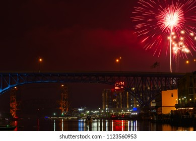 CLEVELAND, OH - JULY 4, 2016: A burst of pink of fireworks ascends over downtown Cleveland's new Flats East Bank entertainment district along the Cuyahoga, with rail and freeway bridges visible.