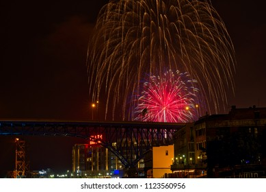 CLEVELAND, OH - JULY 4, 2016: A dramatic display of fireworks bursts over downtown Cleveland's new Flats East Bank entertainment district along the Cuyahoga, with rail and freeway bridges visible.