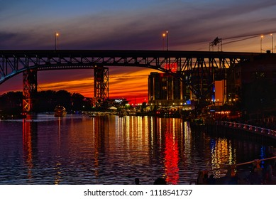 CLEVELAND, OH - JULY 4, 2017: The Cleveland waterfront on the Cuyahoga River downtown lights up just after sunset in anticipation of fireworks soon to come.