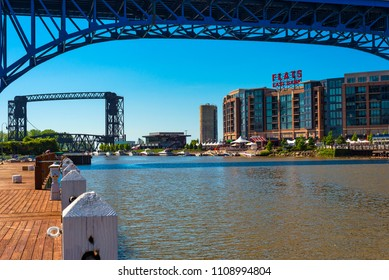 CLEVELAND, OH - MAY 25, 2018: The recently developed Flats East Bank entertainment complex rises on the Cuyahoga River as seen from the west bank, with the Main Avenue highway bridge overhead.