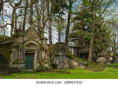 CLEVELAND, OH - MAY 5, 2018: A row of old  mausoleums stands under evergreens in Cleveland's Lakeview Cemetery, a popular attraction with many famous burial sites.
