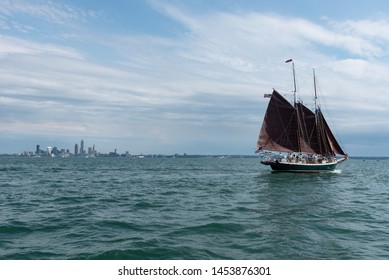 Cleveland, Ohio - USA/ July 11 2019: Tall Ships Parade - small sail boat on  Lake Erie with Cleveland in background.