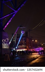 Cleveland, Ohio/USA - February 23 2019: Brite Winter Festival on the Flats under the bridge near downtown. Crowd mingles under disco ball next to glowing bridge with column reading Nikki Forever.