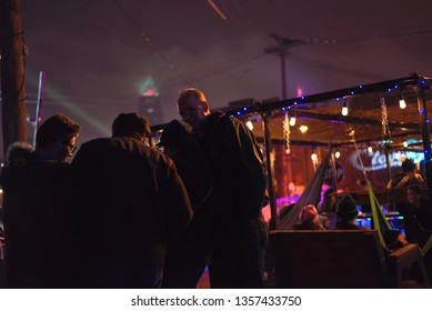 Cleveland, Ohio/USA - February 23 2019: Brite Winter Festival in Flats under the bridge near downtown. Group of friends mingle in front of small shanty tent with soft light. Key Tower in background.