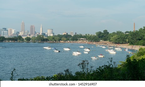 Cleveland, Ohio/USA - July 4, 2019: Wide Angle View Of Edgewater Beach From The Park With Beach Goers And Boats Lining Lake Erie Near Downtown Cleveland's Skyline.