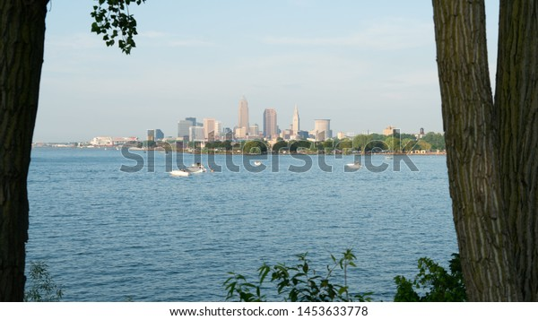 Cleveland, Ohio/USA - July 4, 2019: Looking Through The Trees At Edgewater Park, Cleveland's Beautiful Skyline Lies Just Beyond Lake Erie.