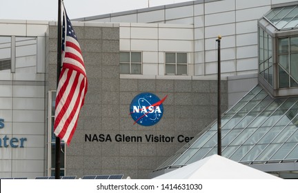 Cleveland, Ohio/USA - June 1, 2019: The Great Lakes Science Center, Also Home To The NASA Glenn Visitor Center, With Flag And Building Emblem In The Background.