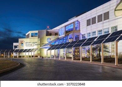 Cleveland, Ohio/USA - March 5th, 2018: The Great Lakes Science Center at night with blue sky and clouds in the background. The modern style building is lit with yellow and blue lights.