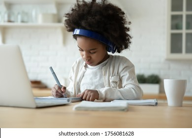 Clever African schoolgirl excellent pupil sit in kitchen do homework wears headphones writing on workbook listen audio lesson use laptop. Videocall, e-study with tutor distantly, homeschooling concept
