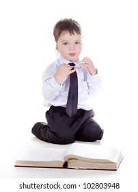 clever boy with a book and wearing glasses isolated in studio