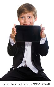 The clever boy, dressed in a tuxedo, holds a tablet in his hand, isolated