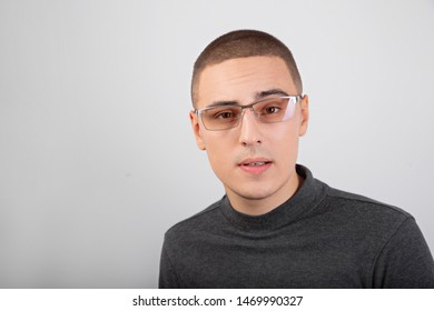Clever business thinking young man looking in camera in fashion glasses in casual clothing on blue background. Closeup portrait