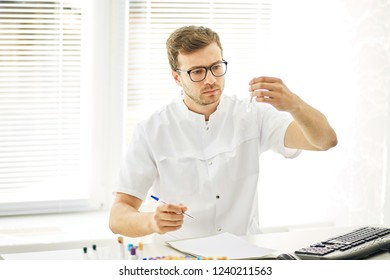 clever doctor with test tube. close up photo. man studing the blood at workplace. new life. family doctor at work