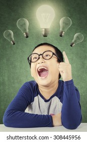 Clever elementary school student wearing glasses and find a solution, pointing at bright light bulb