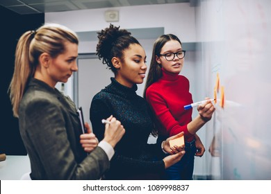 Clever female student writing on board her idea for explaining to colleagues, multiracial crew of employees team working on startup using flip chart for planning successful strategy and discussing