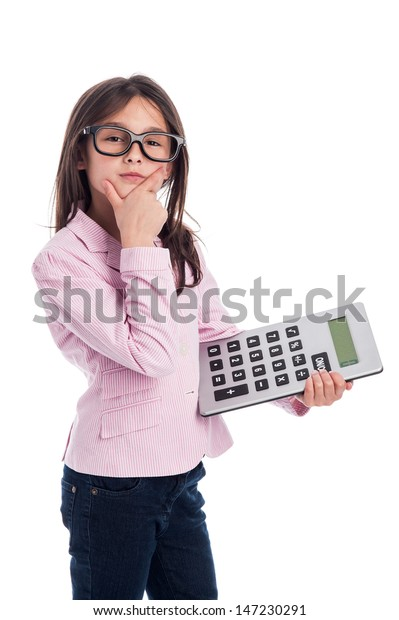 Clever girl with glasses and a calculator doing a calculation. Isolated on a studio white background.