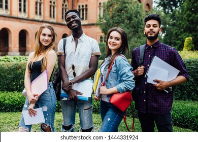 Clever group of smiling students walking together walking near college and hugging.