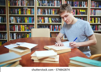 Clever guy sitting by desk in library, reading book and making notes in copybook