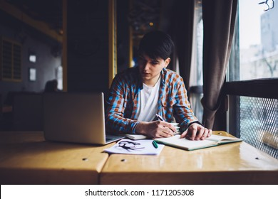 Clever hipster guy looking at laptop device and writing down information in notepad.Pensive young man noting text in notebook while watching interesting webinar online on computer sitting in cafe