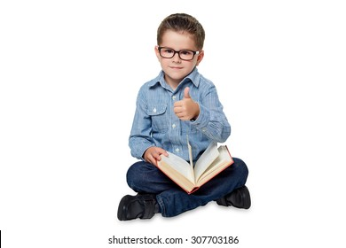 A clever little boy in the blue shirt with book is sitting on the white background.