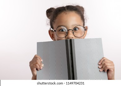 clever little girl with hairbunds and round glasses hiding behind the notepad. kid is playing hide and sick. genius concept