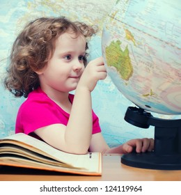 Clever little girl looks at the globe