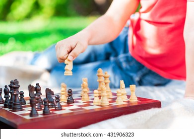 Clever male child is playing chess outdoors