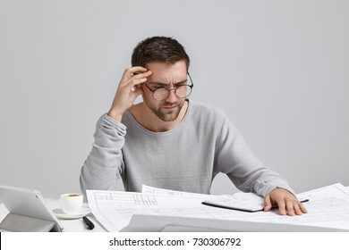 Clever male creative worker tries to concentrate on drawings, doesn`t understand where is his mistake, looks puzzled. Indoor shot of unshaven man in round spectacles being busy with making sketches