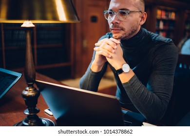 Clever male writer concentrated on idea for bestseller working in library with wifi connection and book archive, young professor in spectacles analyzing information for project making researches