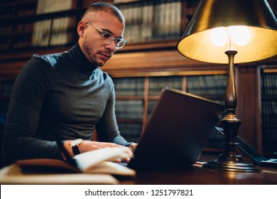 Clever male writer concentrated on idea for bestseller working in library with wifi connection and book archive, young professor in spectacles analyzing information for project making research
