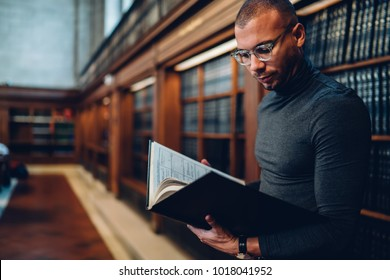 Clever professional lawyer spending time on learning laws in juridical literature in public library, concentrated man journalist reading nonfiction book analyzing information standing news bookshelf