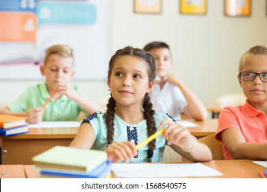 Clever schoolchildren studing and answer questions in classroom at school
