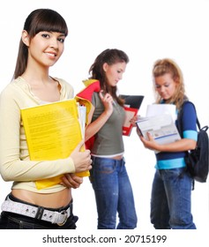 Clever student holding yellow folder in hands - focus on foreground. On background standing  classmates.