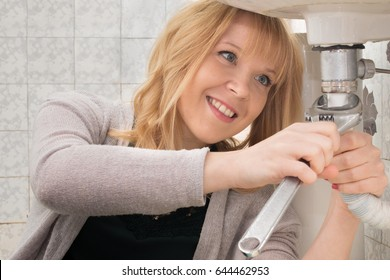 clever woman repairing her bathroom sink pipe with a toothy smile and positive attitude. using a work tool. working middle class woman trying to save money doing repairs herself. DIY concept