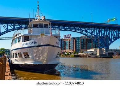 CLEVLEAND, OH - MAY 25, 2018: The Nautica Queen, a popular ship for dinner cruises on the Cuyaghoa River and Lake Erie, is moored before the Main Avenue Bridge and Flats East Bank entertainment area.