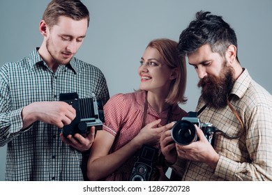 Click with smile. Group of photographers with retro cameras. Paparazzi or photojournalists with vintage old cameras. Retro style woman and men hold analog photo cameras. Photography studio.