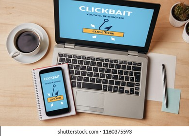 Clickbait concept on laptop and smartphone screen over wooden table. All screen content is designed by me. Flat lay