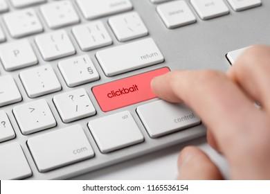 Clickbait (click-bait) headlines internet concept. Computer user press keypad on keyboard.