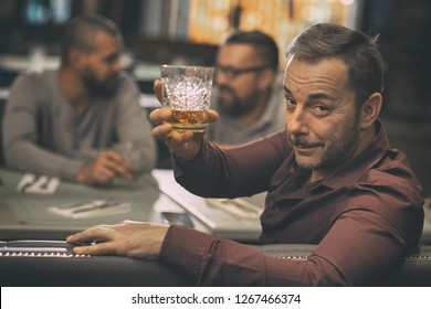 Client of bar looking back through shoulder at camera. Man holding and showing crystal glass of scotch in hand. Man sitting with friends together and tasting good alcohol.