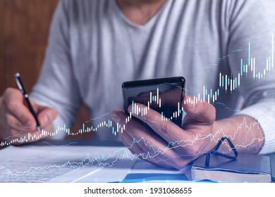 A client in casual wear is signing the contract to invest money in stock market. Internet trading and wealth management concept. Checking the details of transaction at smart phone.