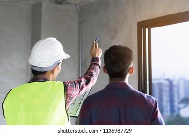 Klient und Vertragspartner diskutieren Plan zur Renovierung Haus.
