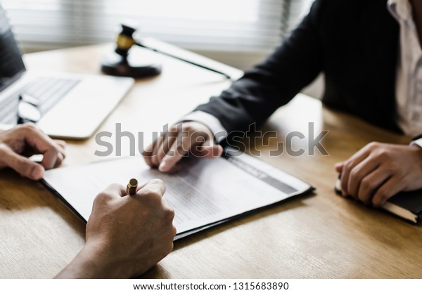 client customer signing contract and discussing business with legal consultants, notary or justice lawyer with laptop computer and wooden judge gavel on desk in courtroom office, legal service concept