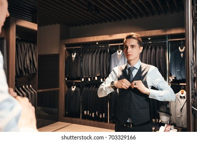 client is elegant guy trying on a sleeveless jacket in a mirror shop. In the background classic suits and jackets