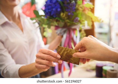 Client giving payment for flowers to saleswoman