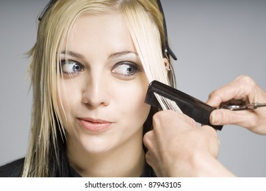 Client looking at comb while hairdresser cutting hair