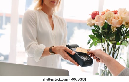 Client making contactless payment with nfc technology credit card at flower shop. Cropped shot with focus on hands making contactless payment.